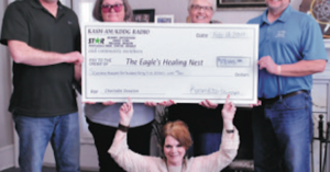 Group holding extra large check made to the Eagles Nest